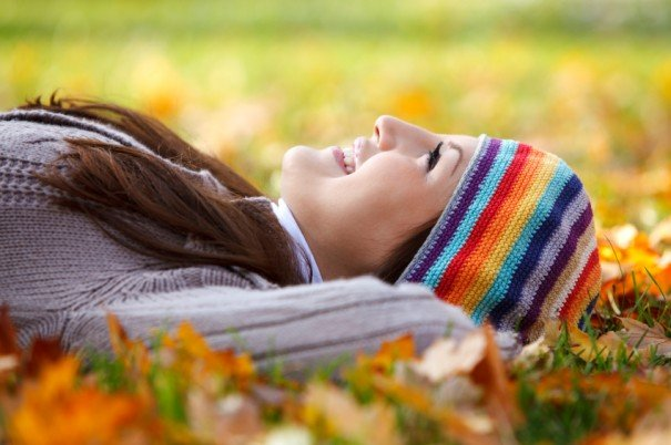 Young woman laying on dry leaves and enjoying life