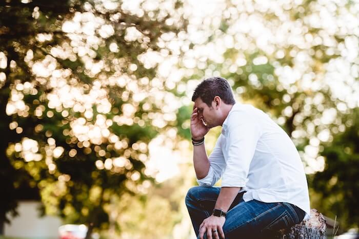 sad man sitting outside how to stop overthinking