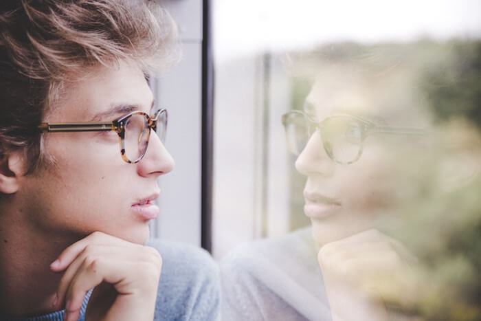 man looking on window benefits of positive thinking