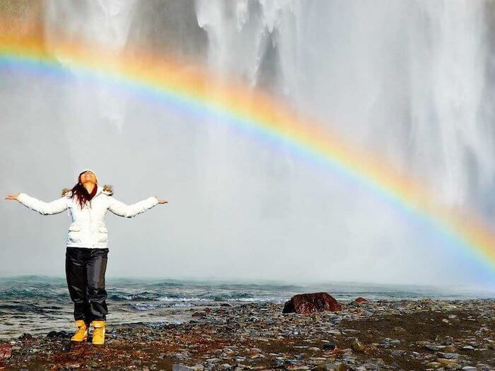 woman beside beach with rainbow benefits of positive thinking