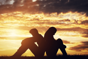 couple sitting at sunset, unhealthy relationship