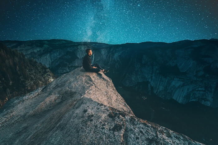 man sitting on mountain peak at dark things to be passionate about