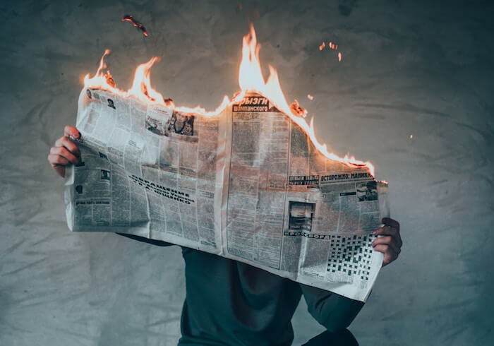 man sitting with newspaper on fire emotional maturity