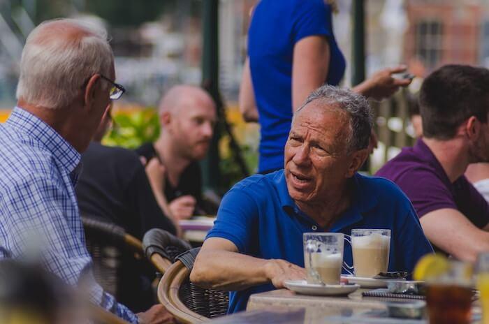 men at table talking constructive criticism