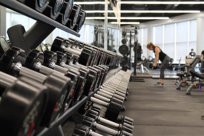 woman lift weights at gym new years resolution ideas