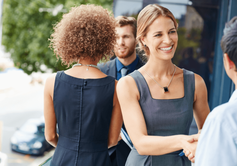 woman shaking hands, how to be more outgoing