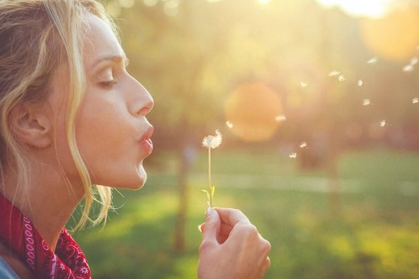 Woman blowing dandelion, key to happiness