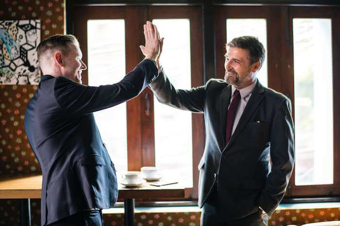 business men high five compliments
