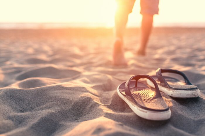 man walking barefoot in sand self-care tips