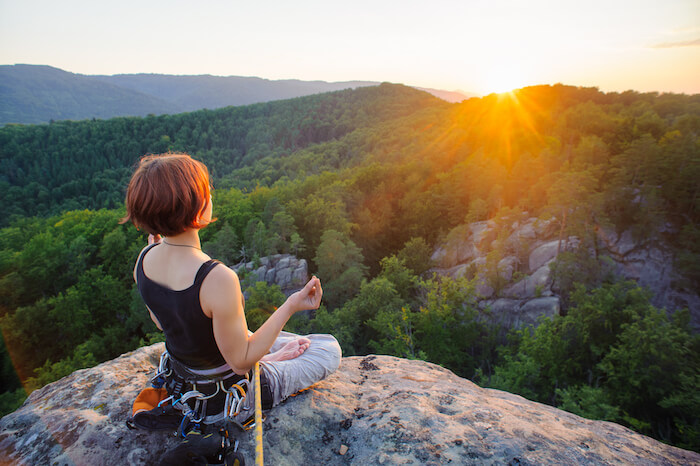 woman meditating mountain top Self-Care Tips