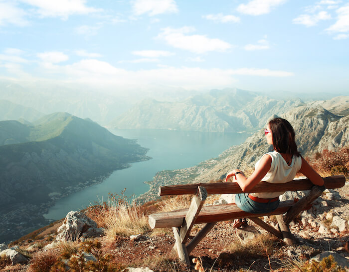 woman sitting on bench mountain top self-care tips