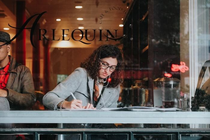 woman in cafe writing in journal Gratitude Journal
