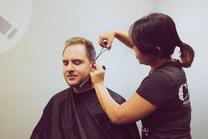 man getting hair cut and beard trim self-improvement