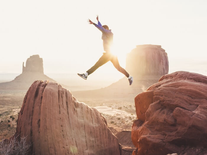 man jumping over rocks life goals