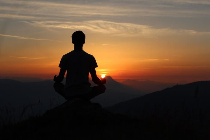 man meditating at sunset how to be a better person