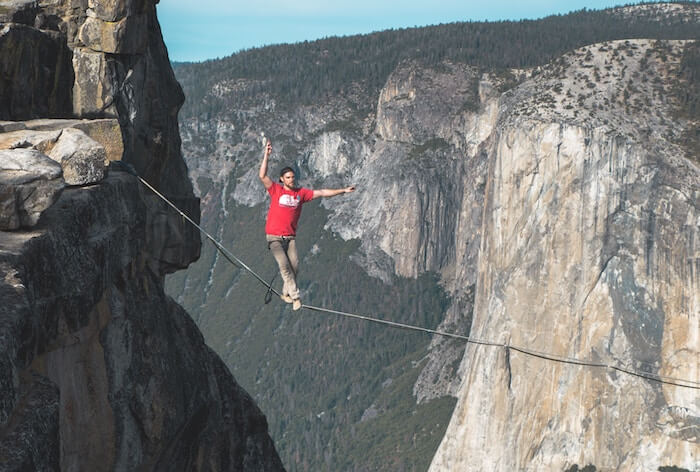 man on tightrope in mountains Live In The Moment Quotes