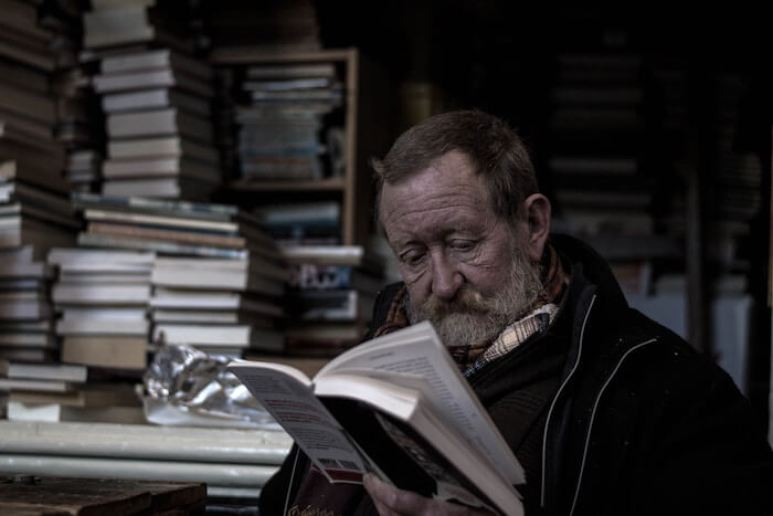 older man reading a book self-improvement