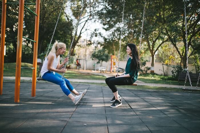 two women sitting in swings laughing best friend tag