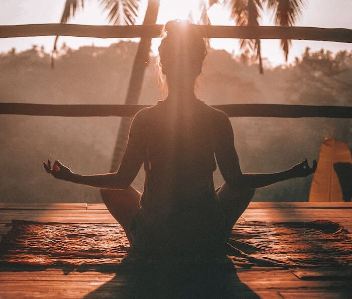 woman meditating at sunset living in the moment