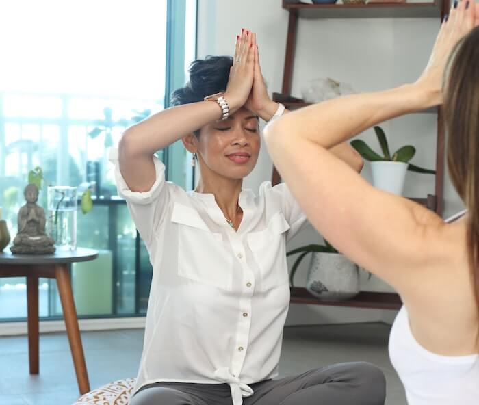 women meditating sitting on pillows self-improvement