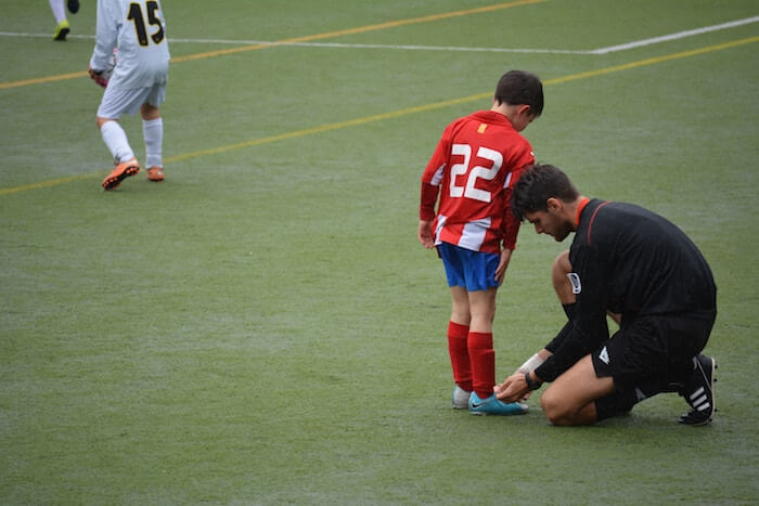 referee helping young player how to be a nicer person