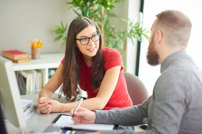 woman and man talking at desk how to end a conversation