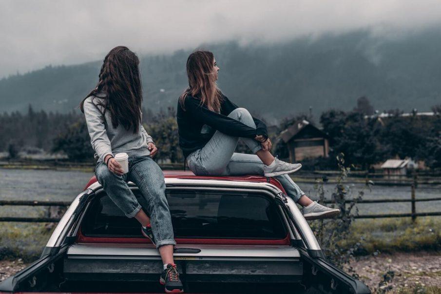 girls sitting on car, pushing people away