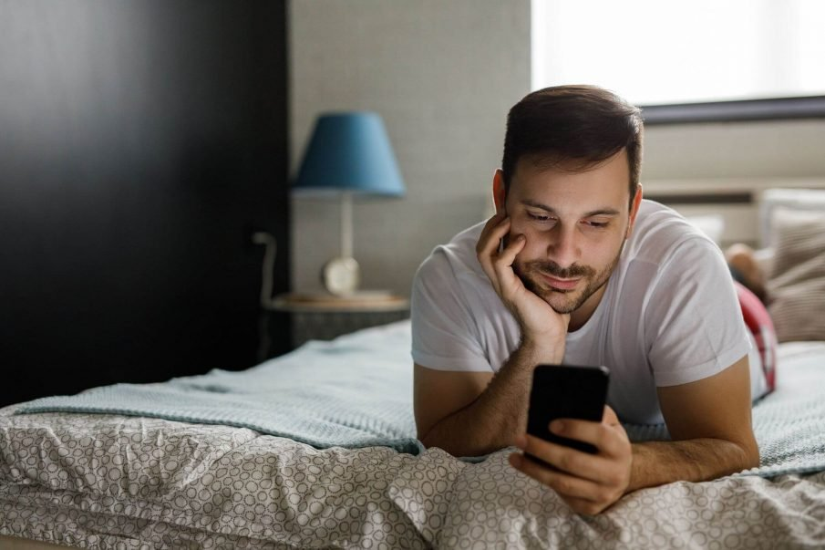 man looking at phone, words of encouragement for men