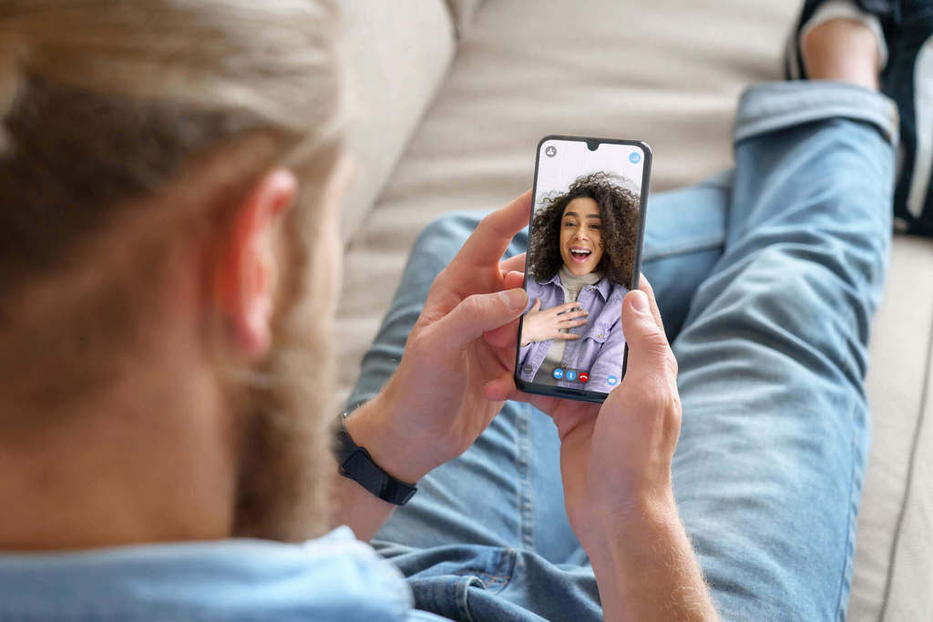 woman sitting on sofa while using phone