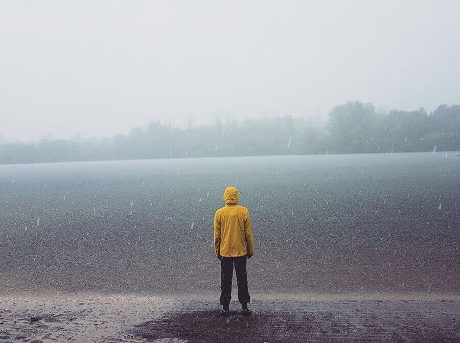 man standing by lake in rain Packable Rain Jackets for Men