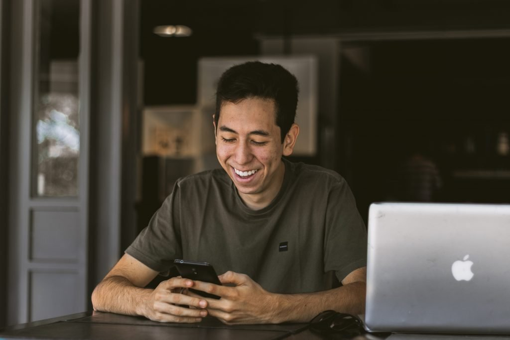 Man smiling while texting Thoughtful And Sweet Long Messages For Her