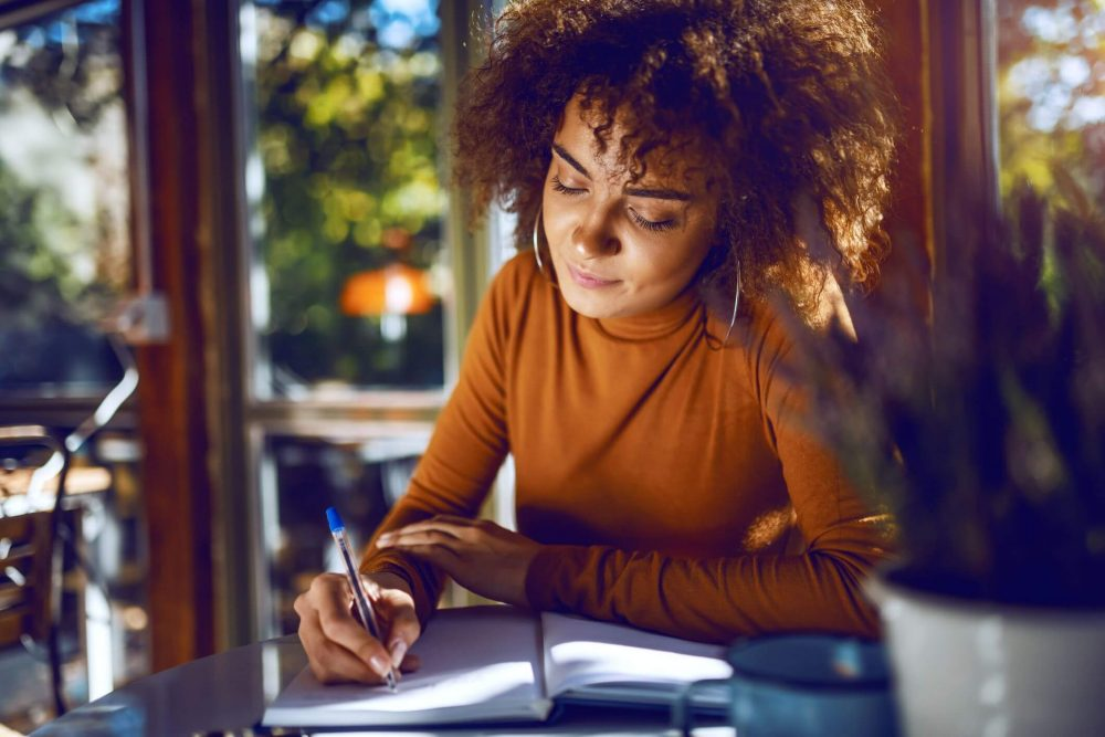 woman writing, mottos to live by