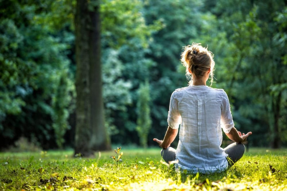 woman meditating, hobbies that make you smarter